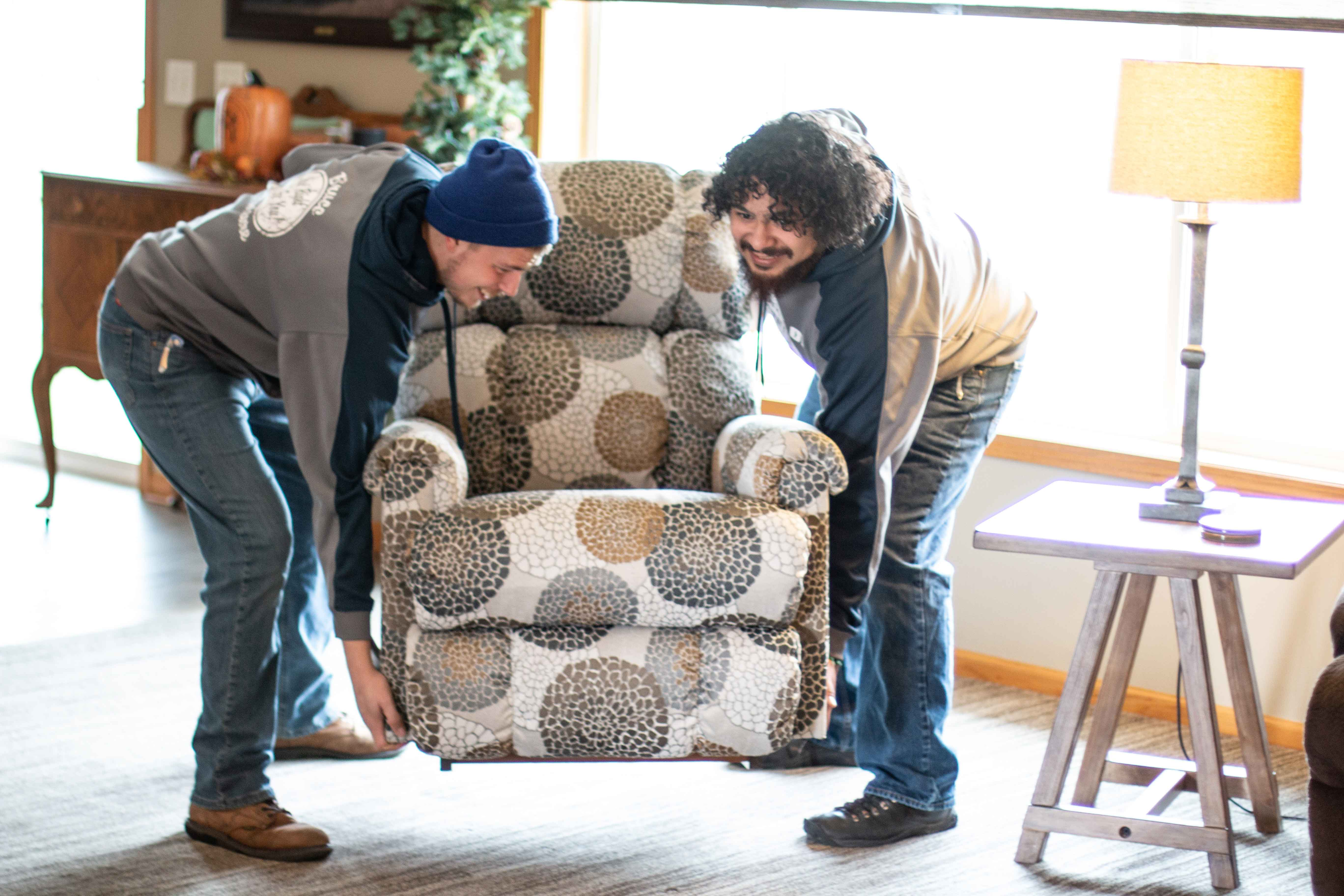 Bruce Furniture employees moving recliner