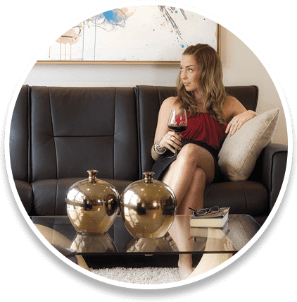 Woman sitting on couch with glass of wine