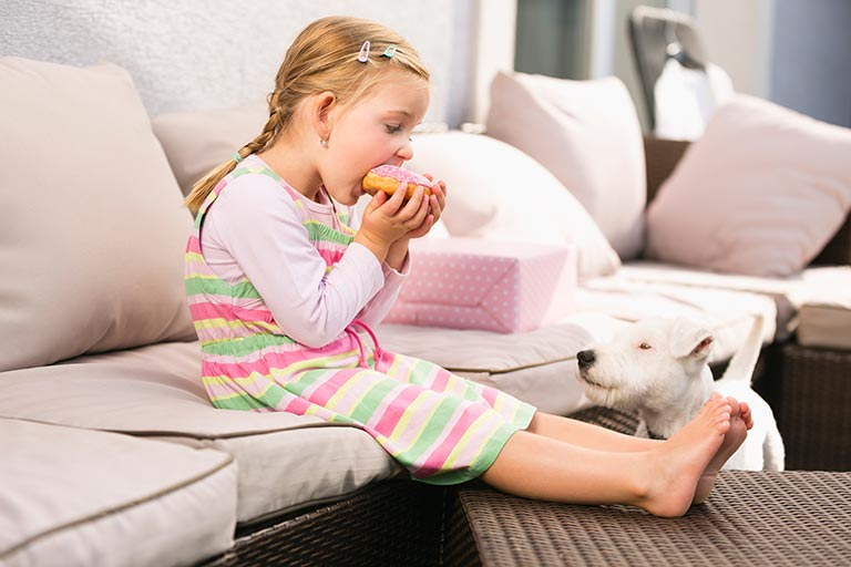 Child eating food on couch