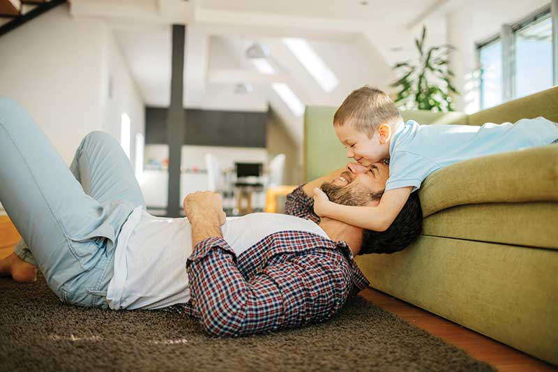 child and dad playing on a couch